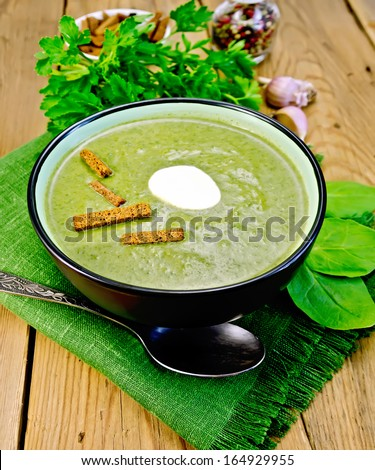 Green soup puree in a bowl with a spoon on a napkin and spinach, parsley, croutons, garlic and pepper on a wooden board - stock photo