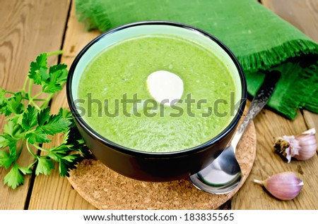 Green soup puree in bowl with a spoon on a stand, napkin, parsley, garlic and pepper on a wooden board - stock photo