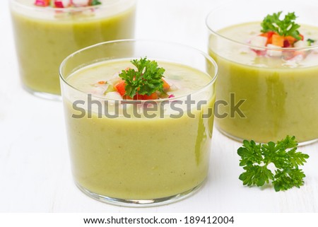 green soup with fresh vegetables in glasses, close-up, horizontal
