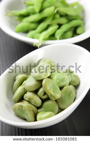 Green soy beans in and out of pods across two white dishes. - stock photo