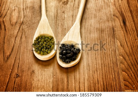 Green soybeans and mexican black beans on wooden background, biologic agriculture - stock photo