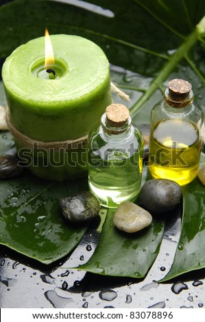 Green Spa-candle and massage oil with stones on leaf - stock photo