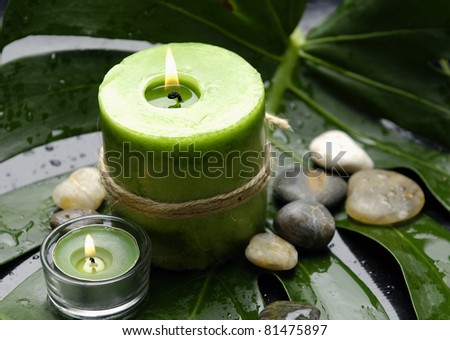 Green Spa-candle and stones on leaf - stock photo