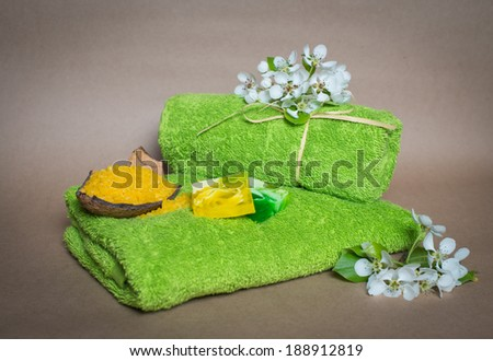 Green spa towels with flowers, aroma soap and salt. - stock photo