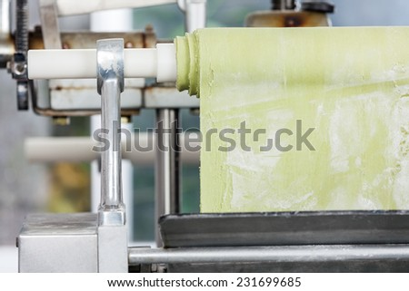 Green spaghetti pasta sheet being processed in machine at commercial kitchen - stock photo