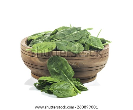 Green spinach in wooden bowl on a white background - stock photo