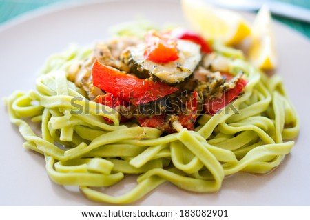 green spinach pasta with stewed vegetables - stock photo
