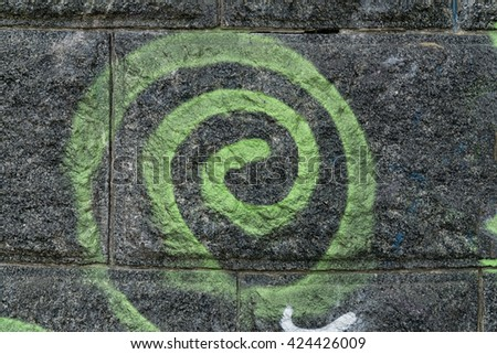 Green spiral on black wall. Detail of a graffiti art on a wall. Wall painted in different colors. Abstract background.