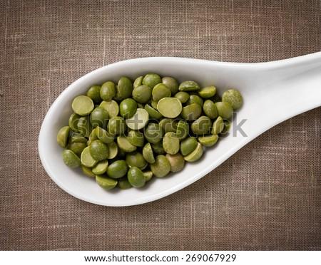 Green split peas in white porcelain spoon / high-res photo of grain in white porcelain spoon on burlap sackcloth background - stock photo