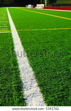 Green sports field with artificial grass and racetrack - stock photo
