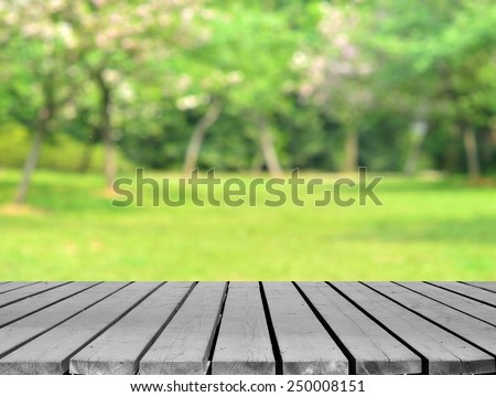 Green spring background with empty wooden platform - stock photo