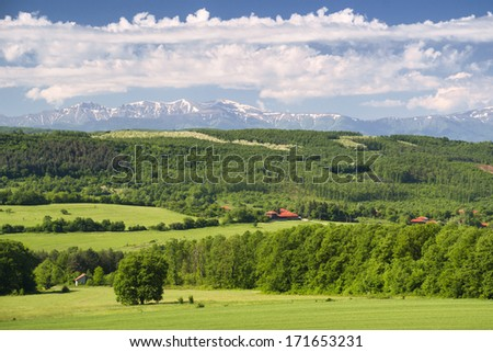 Green spring fields, forest and a small village with high mountain tops still covered with snow on a clear, sunny day in Bulgaria. - stock photo
