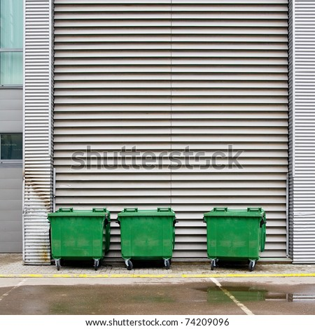 Green street dumpsters against tin wall - stock photo