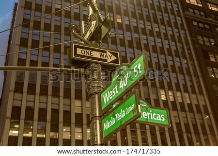 Green street signs of New York City at dusk, with building on background - stock photo