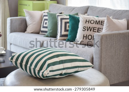 green striped pillows on the cozy grey sofa in the living room - stock photo