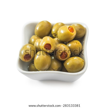 Green stuffed olives in white bowl. Studio Shot. Isolated on white.
