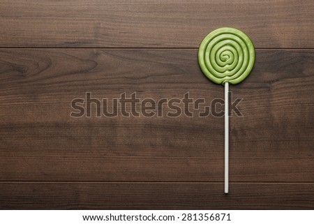green sugar lollipop on the wooden table - stock photo