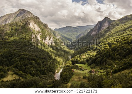 green summer mountains of world's second largest canyon of Tara river in Montenegro with white clouds on blue sky landscape - stock photo