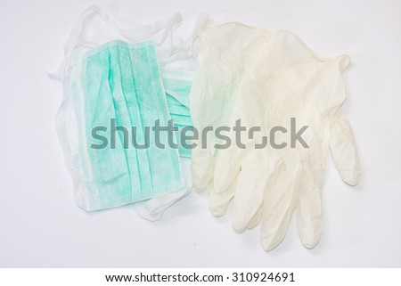 Green surgical mask and white gloves. - stock photo