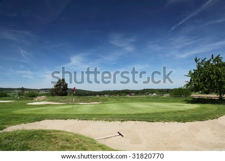 green surrounded with bunkers with dramatic summer sky - stock photo