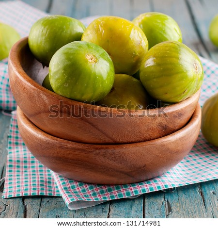 Green sweet fig in the wooden bowl - stock photo