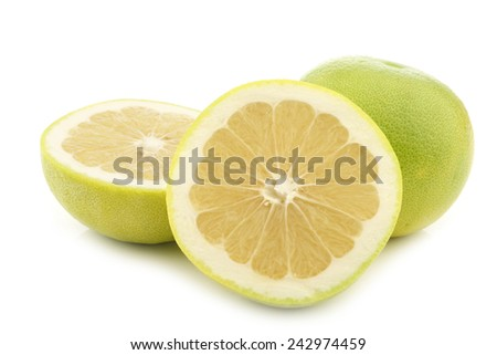 green sweet grapefruit and a cut one on a white background - stock photo