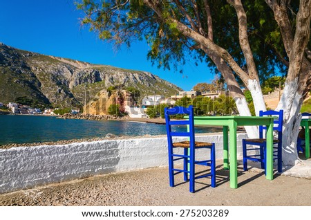 Green table with blue chairs and typical white wall in romantic Greek bay on sunny day, Greece - stock photo