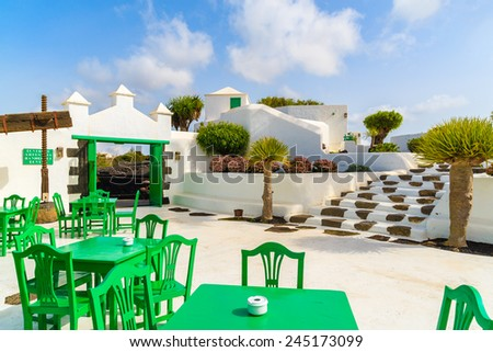 Green tables with chairs in typical Canarian style village, El Campesino Monumento, Lanzarote island, Spain - stock photo