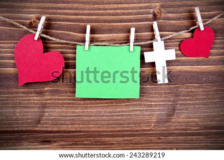 Green Tag Or Label With Hearts And Cross On A Line With Copy Space For Your Free Text Here On Wooden Background, Three Symbols, Vintage, Retro And Old Fashion Style With Frame - stock photo