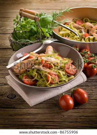 green tagliatelle with norway lobster,  tomatoes and lemon peel - stock photo
