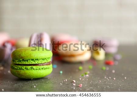 Green tasty macaroon on gray table - stock photo