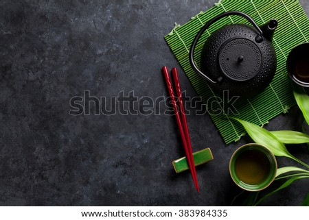 Green tea and sushi chopsticks on stone table. Top view with copy space - stock photo