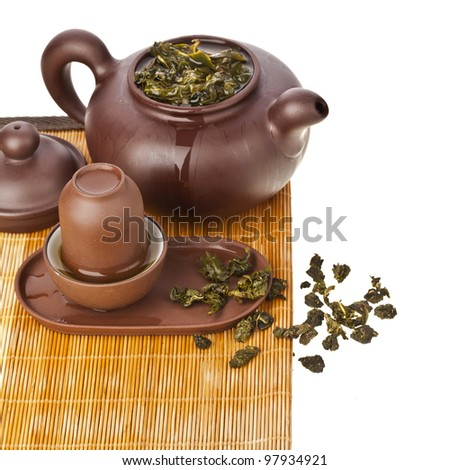 Green tea balls oolong in clay teapot and teacup isolated on white background  - stock photo