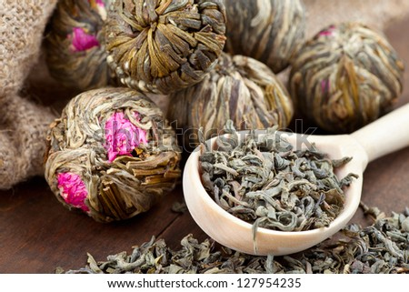Green tea balls with flowers and wooden spoon with tea on kitchen table - stock photo