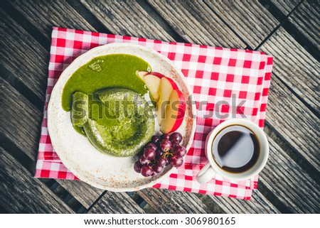 Green tea cake with fruit in plate on wooden - stock photo