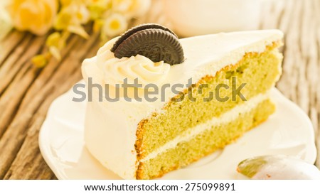 Green tea cream vanilla cake on wooden background soft focus vintage tone. - stock photo