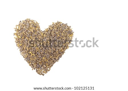 Green tea dried leaves shaped in a heart on a wooden desk.