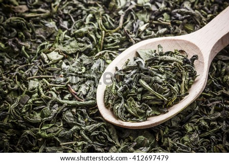 Green tea dry leaves on wooden spoon background.