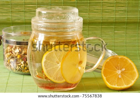 green tea from herbs and lemon on a green background