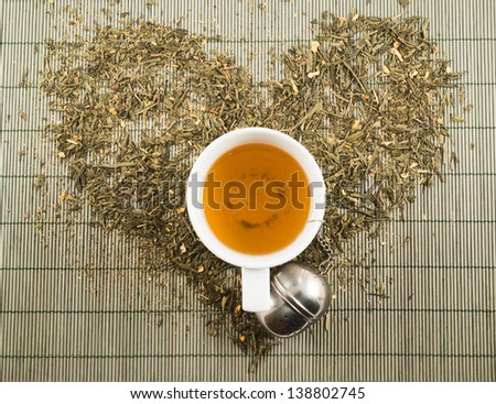 Green tea heart shape over bamboo mat top view with teacup - stock photo