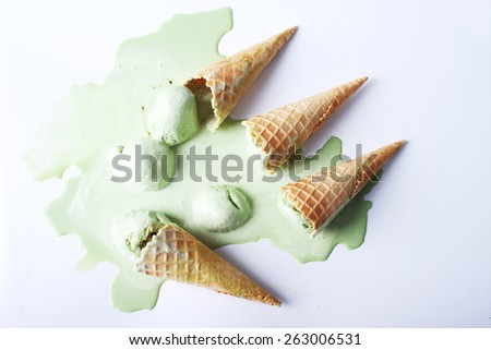 green tea ice cream cones dropped upside down on white background - stock photo