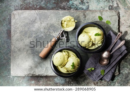 Green tea ice cream with mint leaves and Spoon for ice cream on stone slate background - stock photo