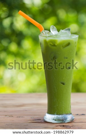 Green tea in a glass on a green background. - stock photo
