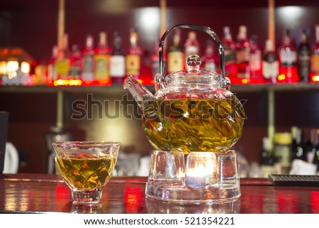 Green tea in a glass teapot on the table