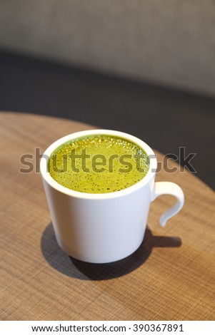Green tea in a white cup on table