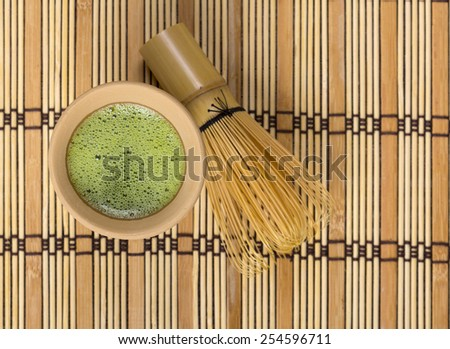 Green tea in clay cup with bamboo whisk - stock photo