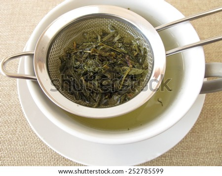 Green tea in tea strainer - stock photo