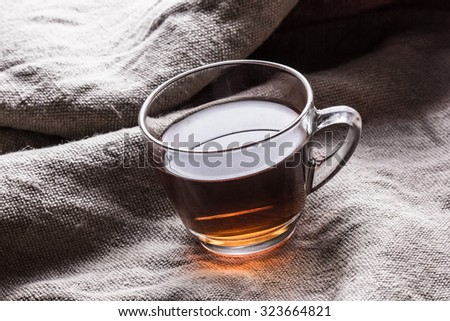 Green tea in transparent glass on linen fabric.