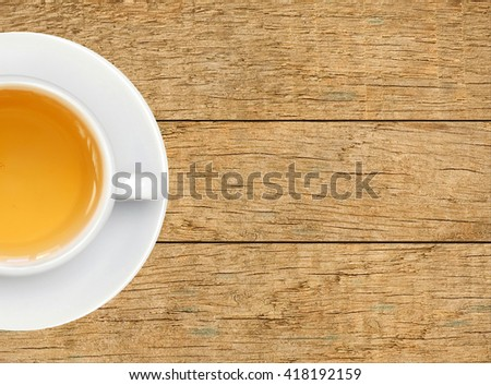 green tea in white cup on wooden texture background