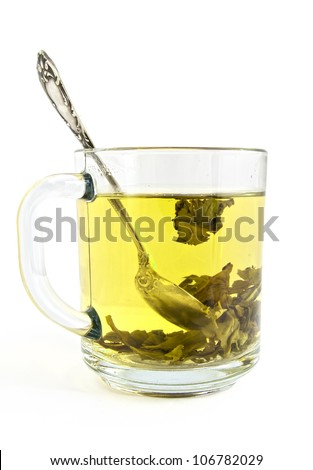 Green tea is brewed in a transparent cup on a white background - stock photo